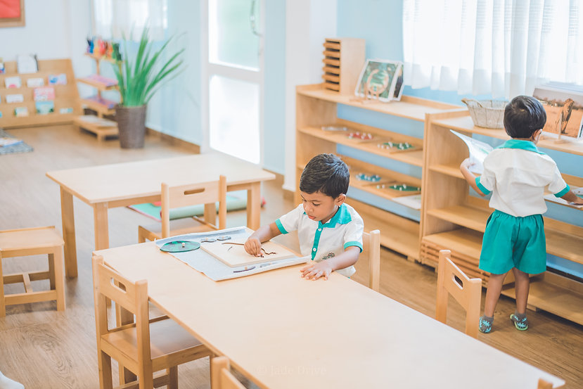 A student from Jade Drive is attempting a Montessori puzzle in the classroom.