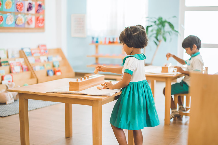 A student from Jade Drive International Preschool, Sri Lanka, attempting a Montessori material, the Knobbed Cylinder.