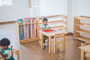 A child from Jade Drive is working on a dressing frame, a Montessori material.