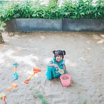 A child is playing at the sand area.