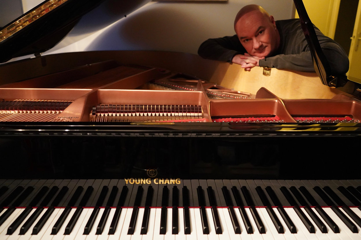 Seamus Kearney at home with his baby grand piano