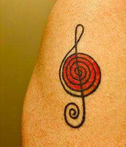 Tattoo behind the logo for Seamus Kearney Piano