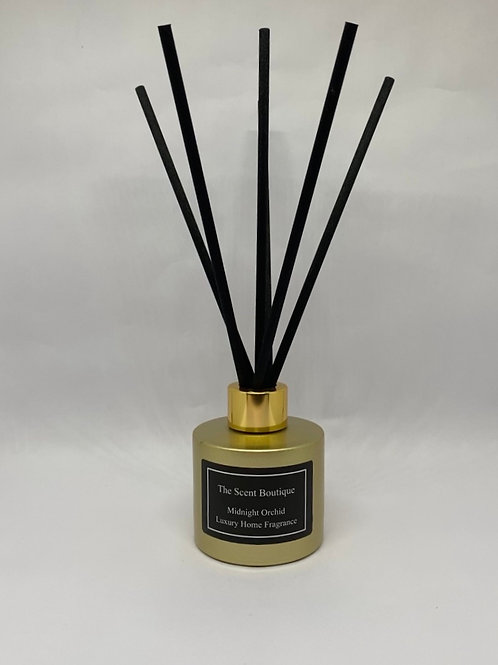 Gold Glass Luxury Reed diffuser with gold cap and black reeds.