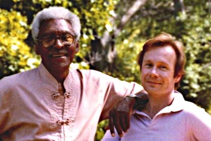 Bayard Rustin, on the left, and Walter Naegle, on the right, smiling and posing for the picture, with a background of trees.
