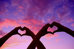 silhouette of hands making hearts against a sunset
