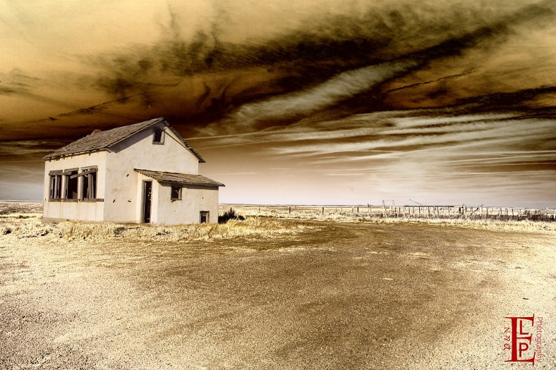 abandoned farm house under dusty sky
