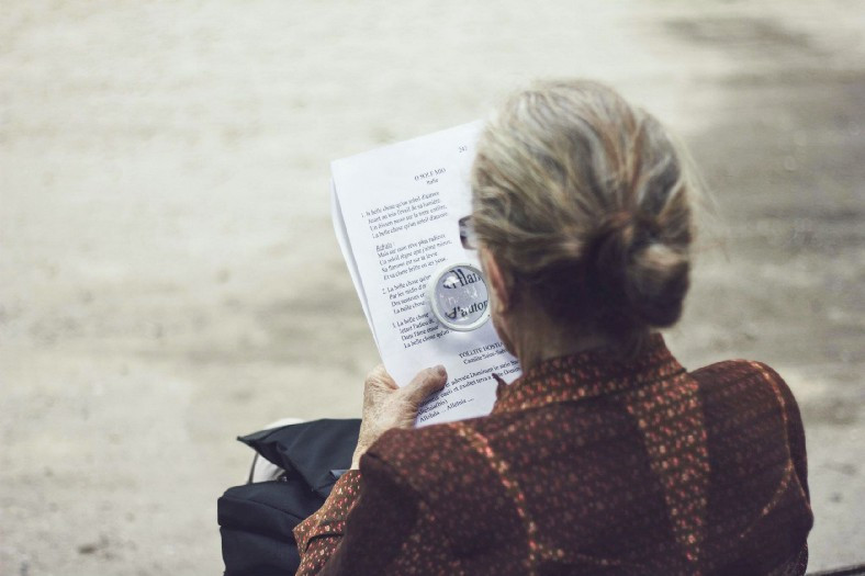 Older woman reading with magnifying glass