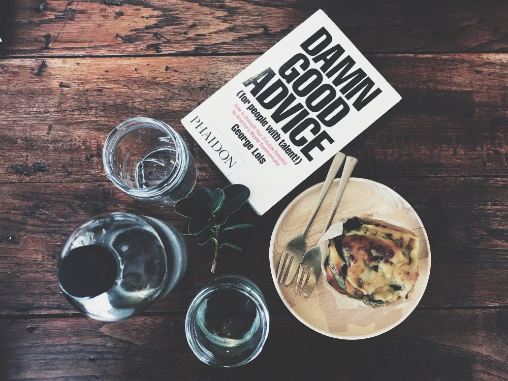 """Table with food and book titled, """"Damn Good Advice."""""""