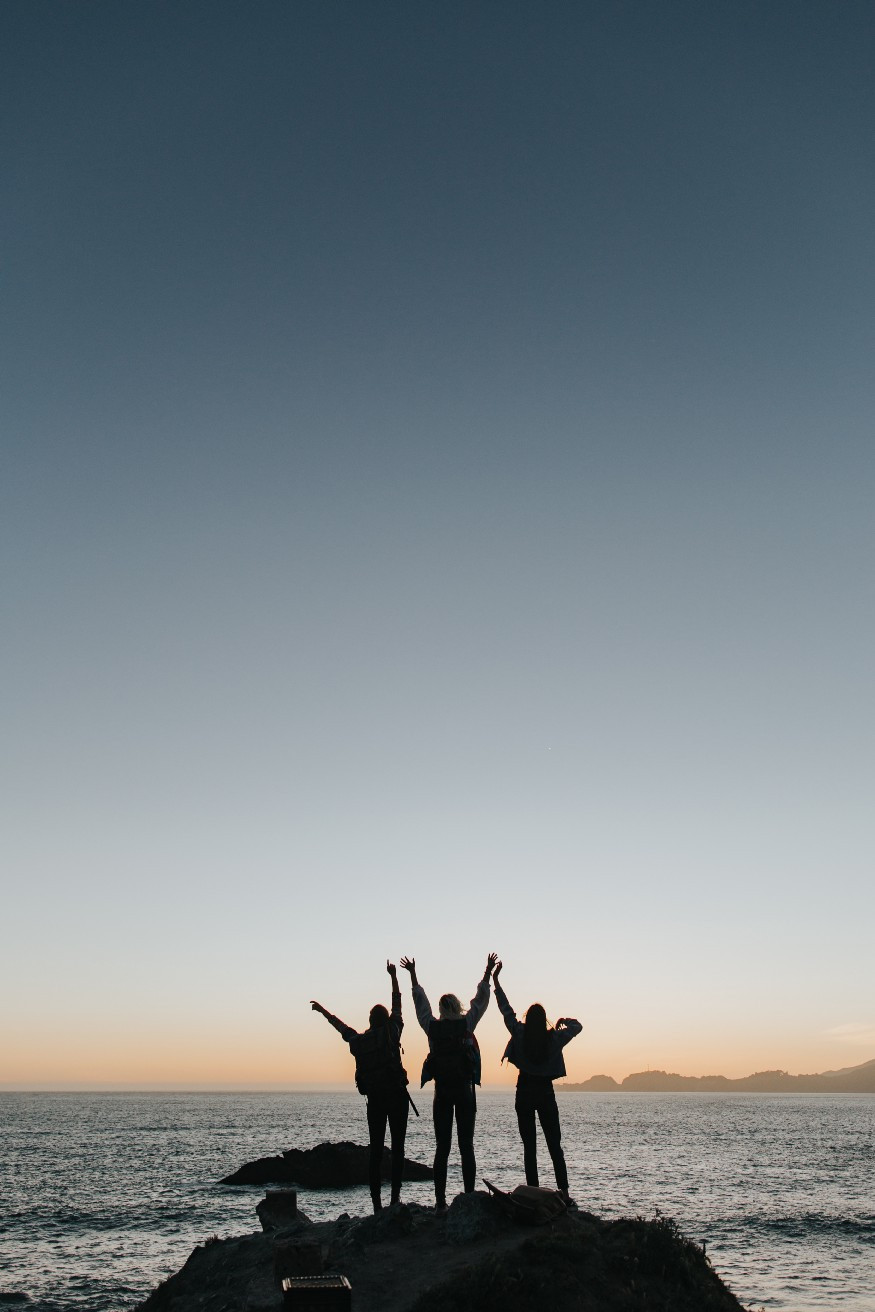 Three friends raising arms in triumph to the sea