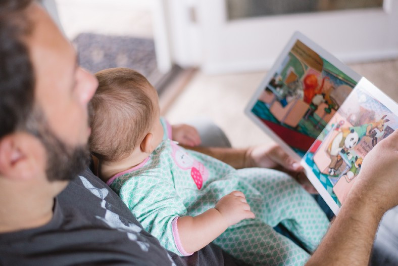 Man reading to infant