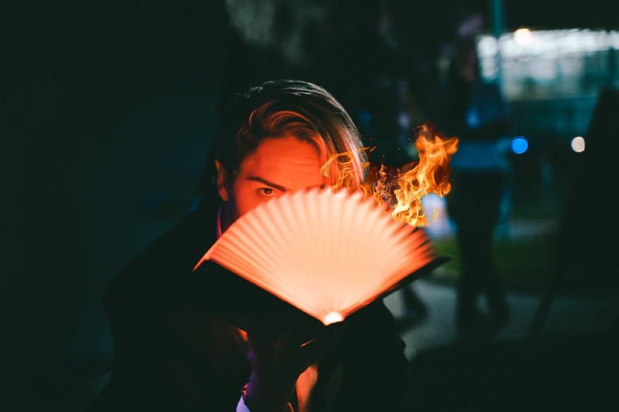 author's eyes peeking out from burning book