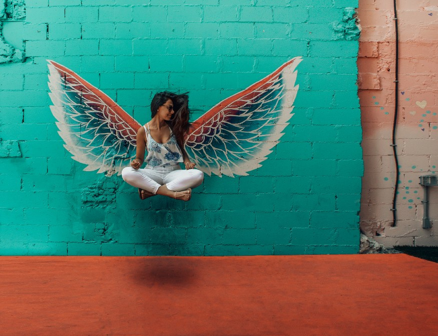 Girl with wings levitating against turquoise wall