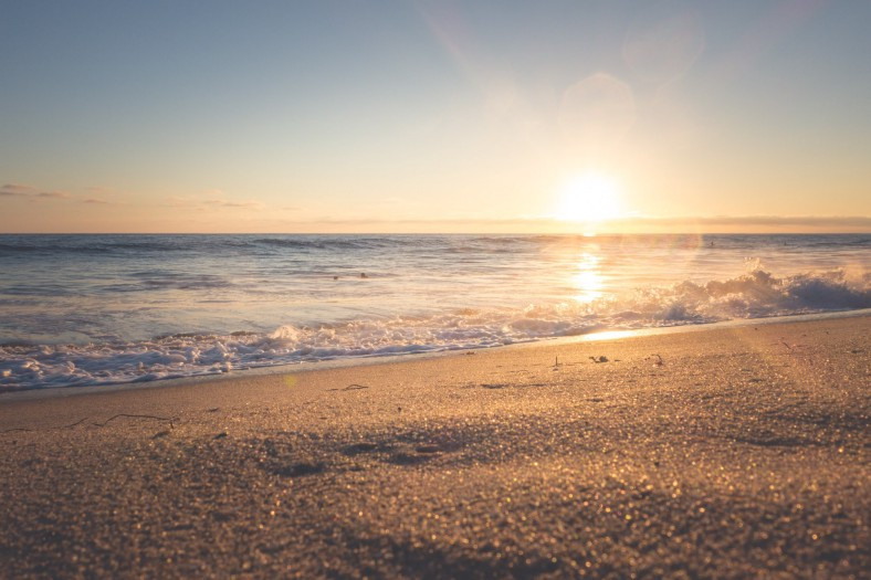 The sun rising over a deserted beach