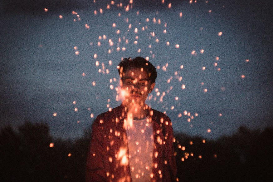 boy sending sparks into a night sky