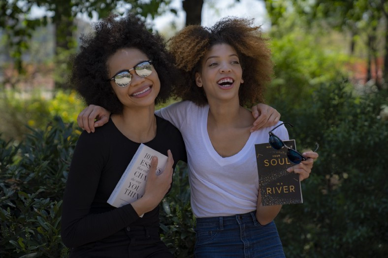 Two girls laughing holding books