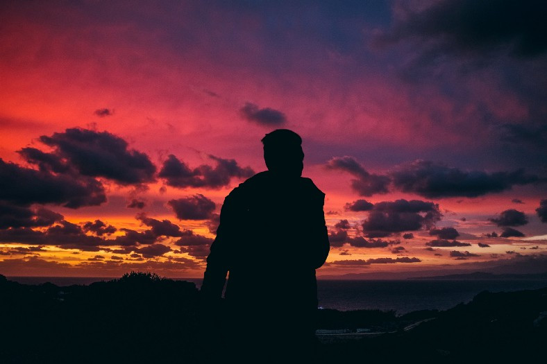Man's silhouette under a scarlet sunset
