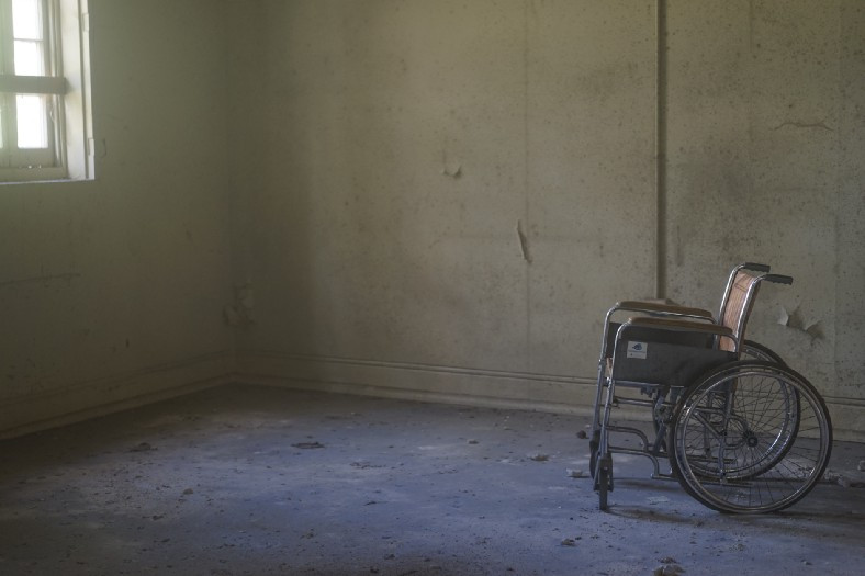 Dingy asylum room with empty wheelchair