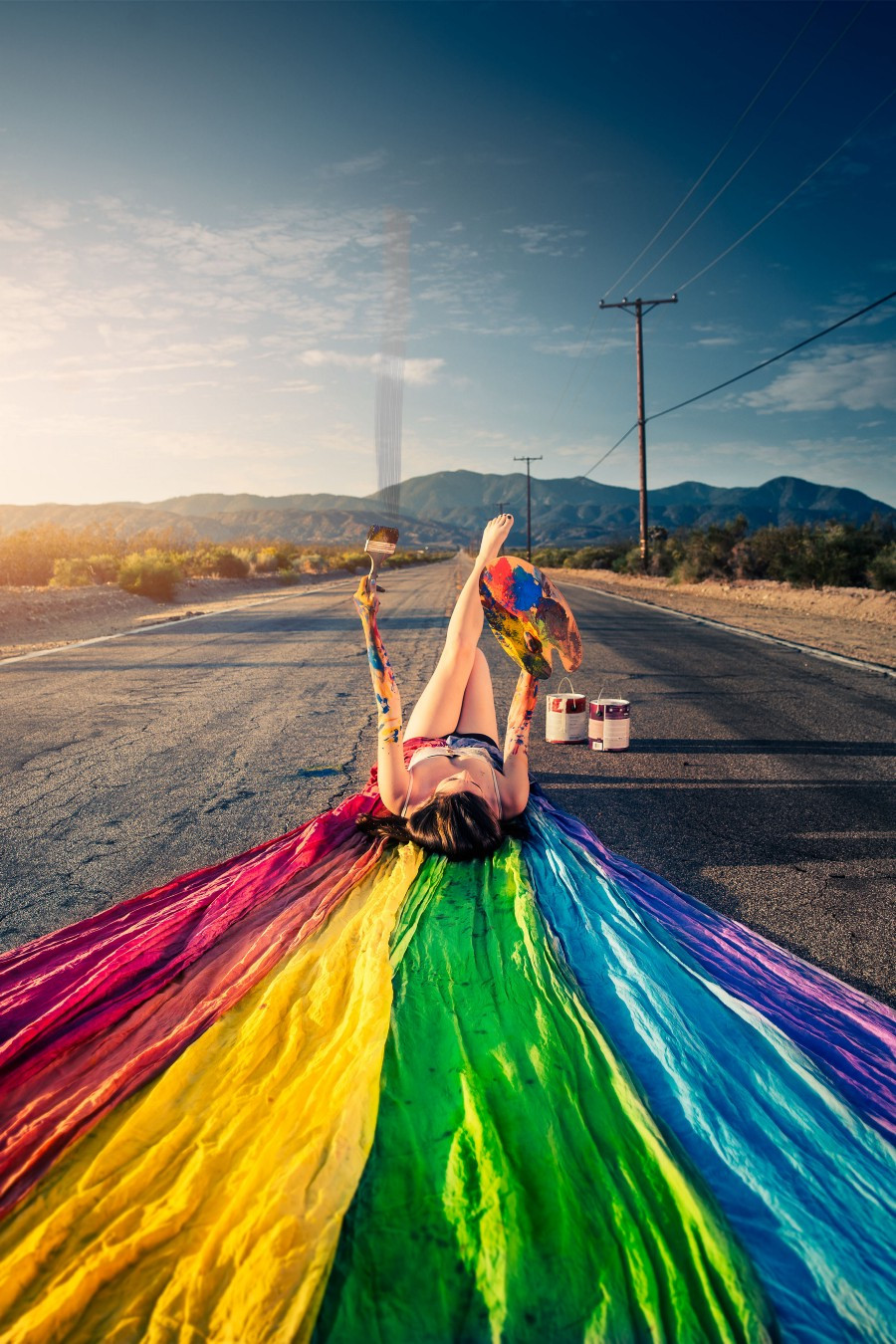 Woman painter lying in road with painted rainbow