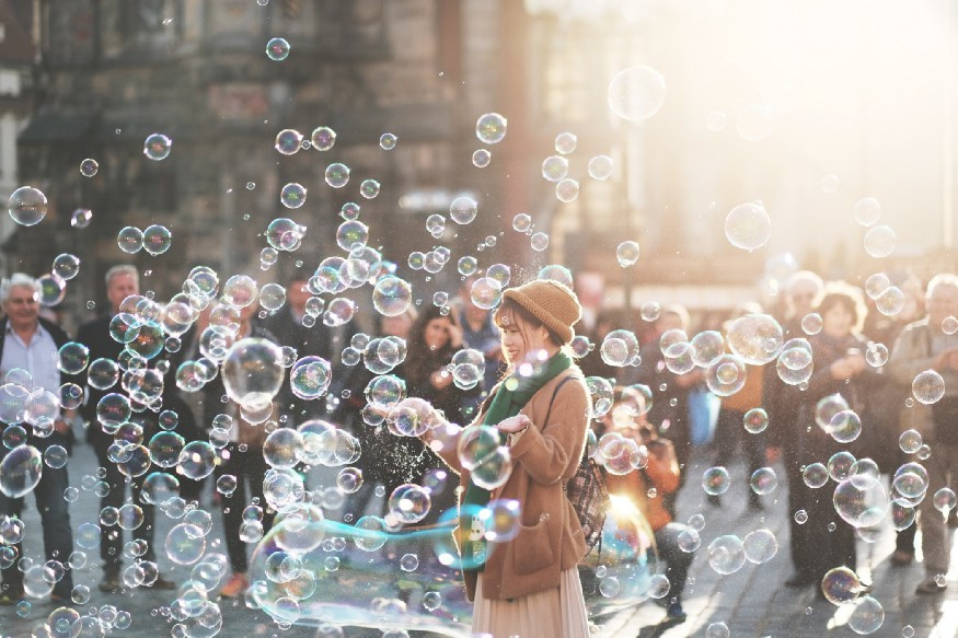 Woman releasing bubbles on crowded street
