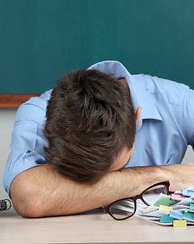 Young teacher sitting in school classroo