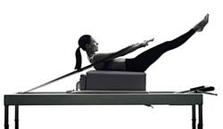 bigstock-woman-pilates-reformer-exercis-140056100