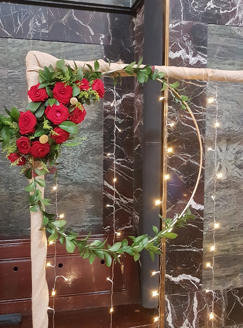 Hoop with fresh red roses and greenery