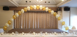 Gold and white arch over top table