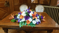 Artificial orange, ivory and purple top table decoration
