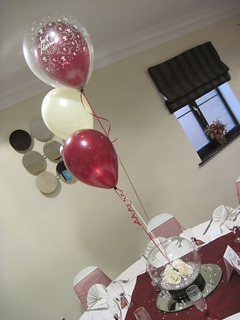 Trio of balloons in large bowl with flowers