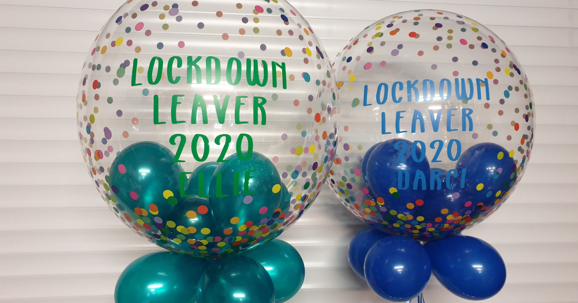 Mulit coloured confetti bubble with one green and one balloons