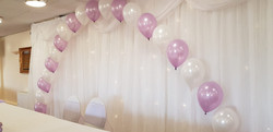 lilac and white arch over top table