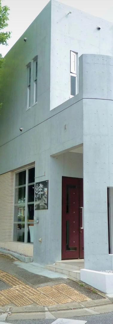 バーカウンターのあるモダン店舗と街路樹の見える住宅