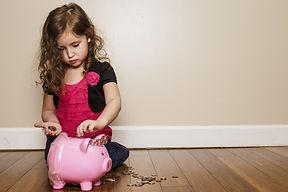 little girl putting money in her piggy b