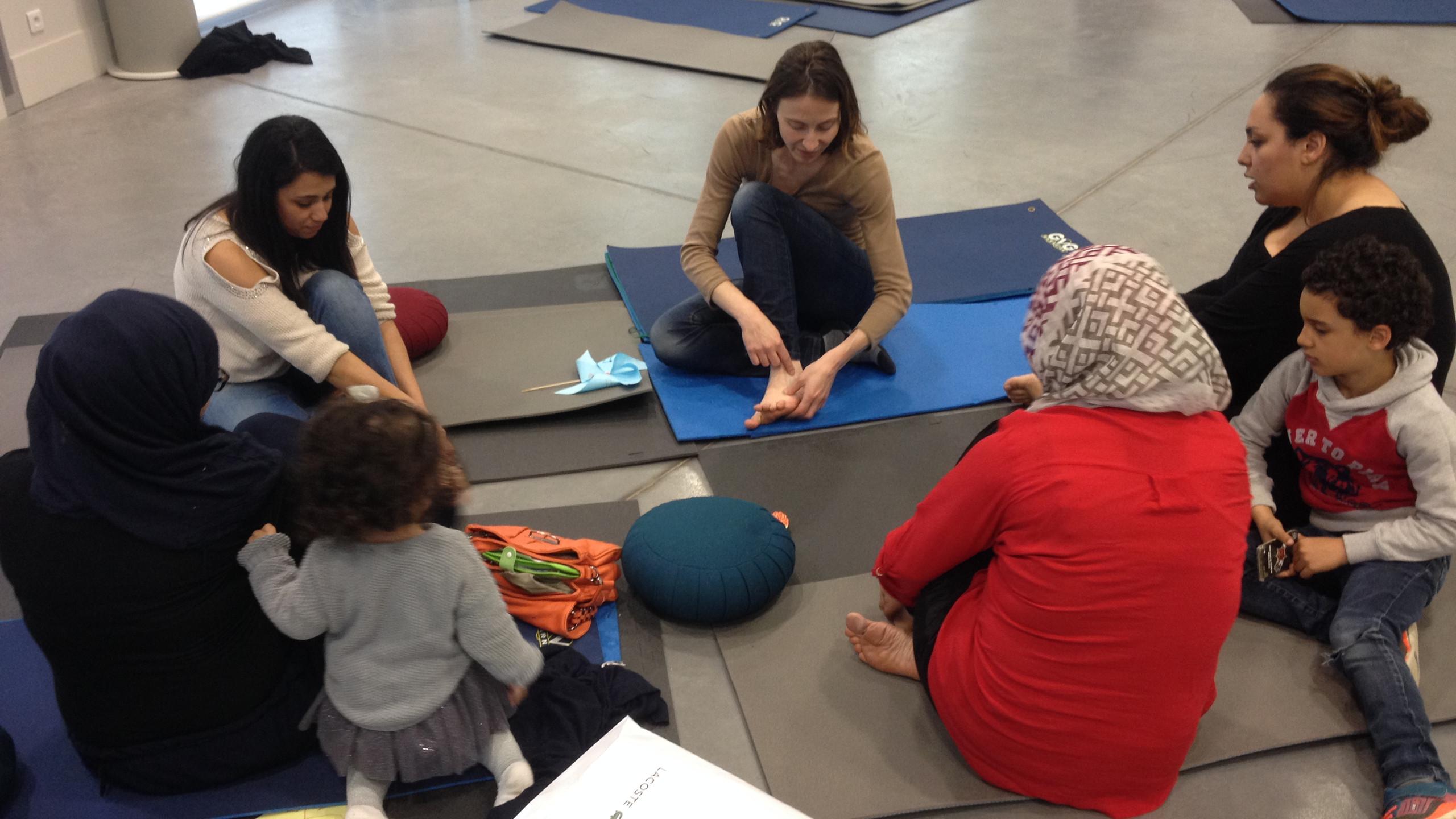 Le Pôle de Thérapeutes en action en train de montrer aux femmes et leurs enfants comment relâcher les tensions de la journée.