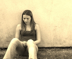 girl sitting by a wall
