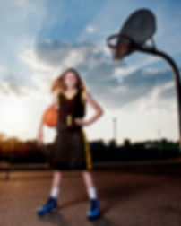 Little girl in black and gold basketball uniform standing next to playground hoop with ball, dramati