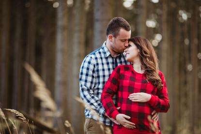 Pár v kostkované style košili při focení bříška těhu v lese