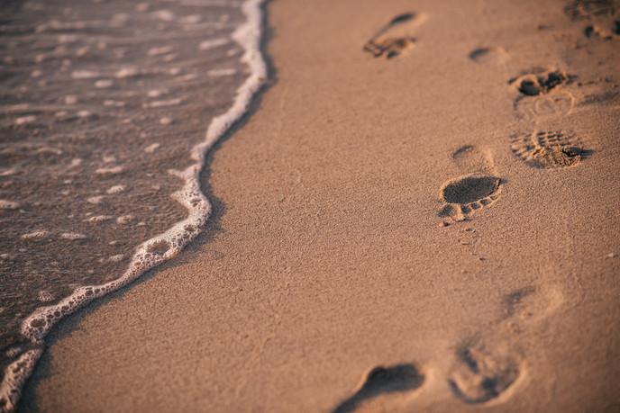 feet in the sand, sea washing it away, mallorca spain