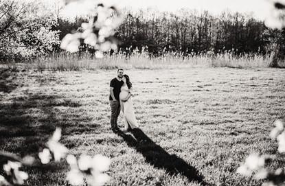 Černobílá fotka dvou nastávajících rodičů při těhu focení skrz třešeň