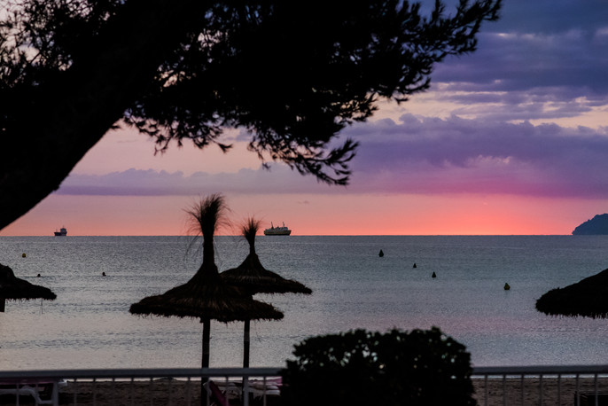 Sunrise over Playa de Muro, Mallorca - pink and purple shades, sun umbrellas and sea