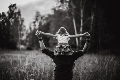 Černobílý snímek tatínka nesoucího dcerku na ramenou v přírodě
