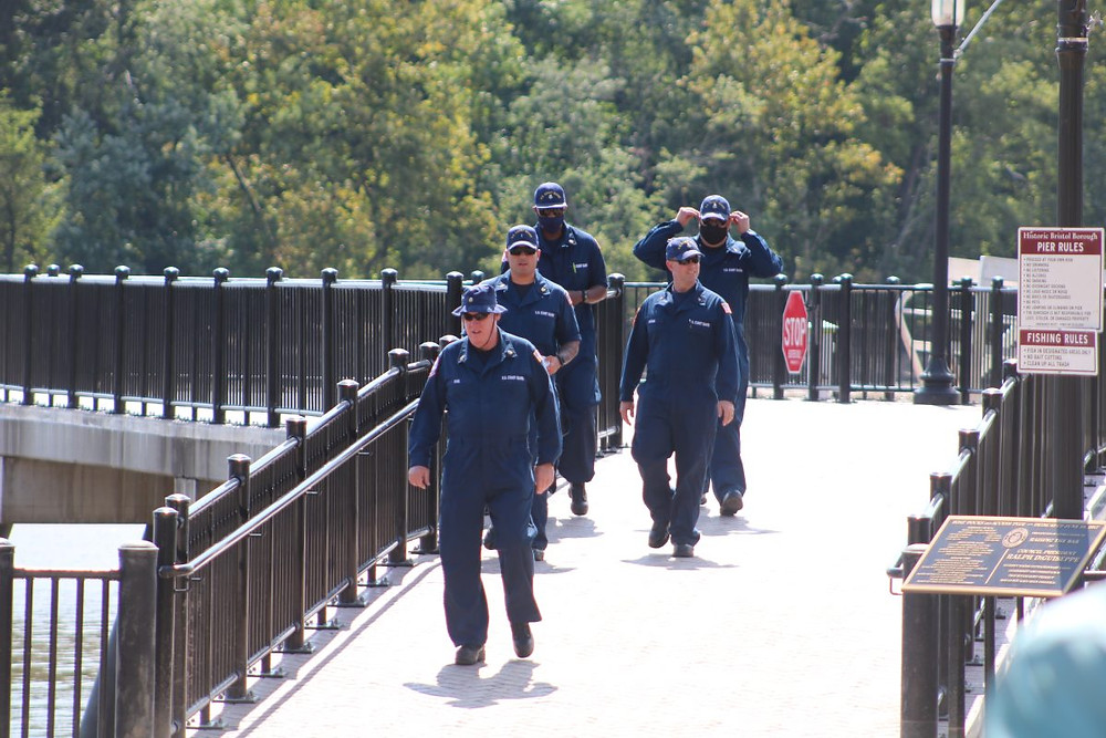 Coast guardsmen walk down the wharf in Bristol Borough