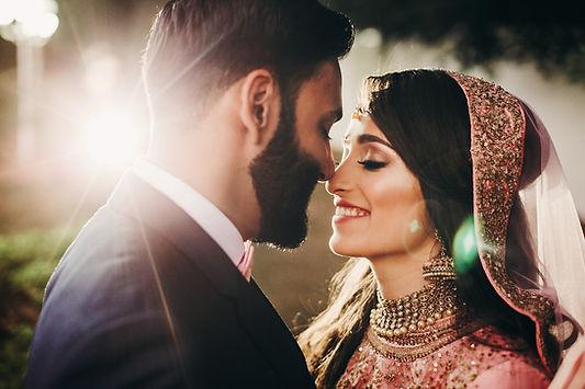 Handsome bearded Indian groom kisses bri