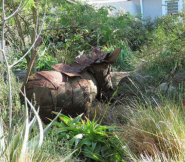 A metal warthog forages in the wild grass