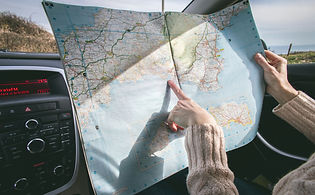 person-wearing-beige-sweater-holding-map