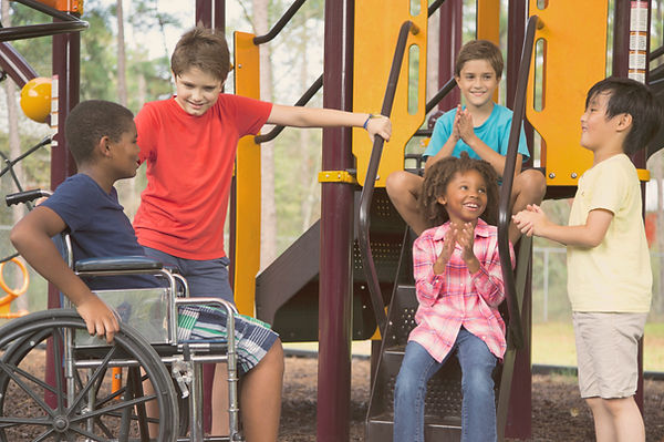 Multi-ethnic Group of chilren in a playground, including a boy in a wheelchair