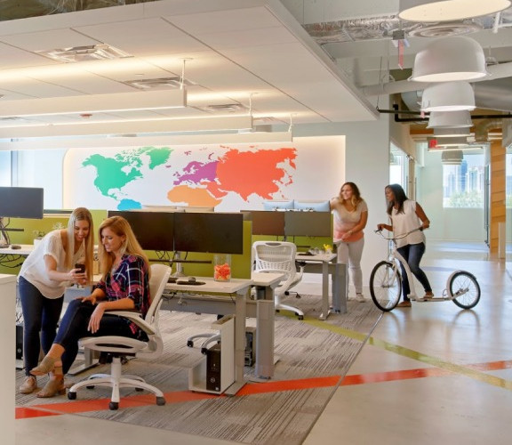 A few Wix employees at the Wix Miami office with a glocal map on the wall