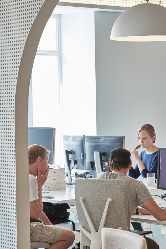 3 Wix employees working next to their computers at the Wix Vilnius office