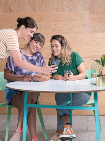 3 Wix employees looking at a mobile screen with excitement
