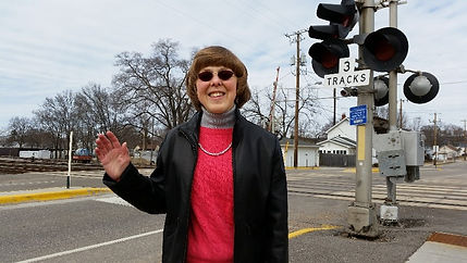 Leone, a woman waving in front of a rail crossing